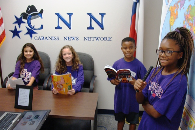 Four students dressed in purple shirts